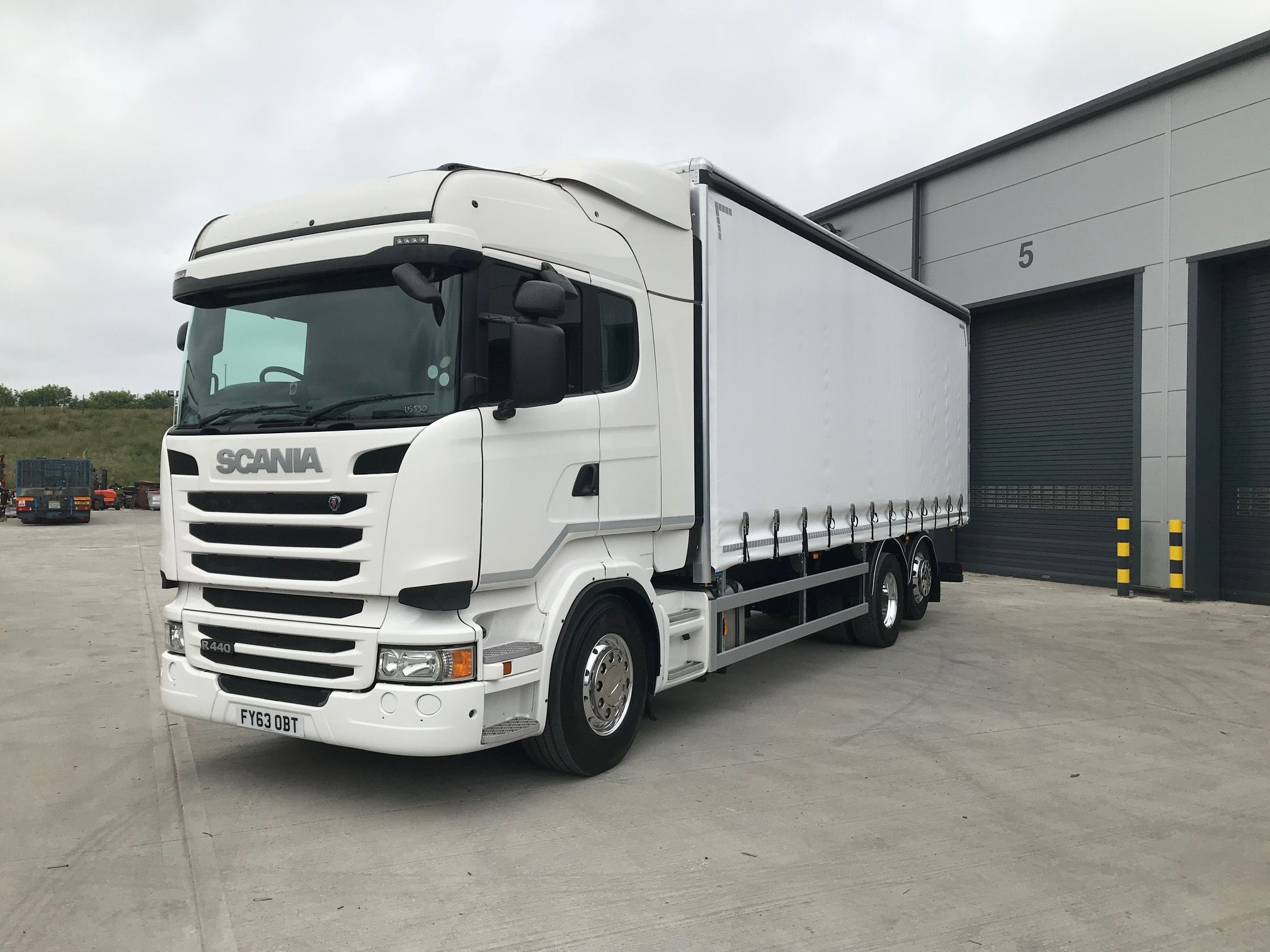 left hand view of white scania curtainsider truck