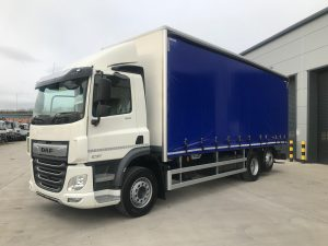 left side view of a blue daf curtainsider truck
